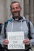 A priest protests outside the Bank of England on the eleventh day of Extinction Rebellion's Impossible Rebellion protests on 2nd September 2021 in London, United Kingdom. Extinction Rebellion activists, who are calling on the UK government to cease all new fossil fuel investment with immediate effect, included over fifty wearing signs indicating that they were breaking restrictive bail conditions by entering the City of London.