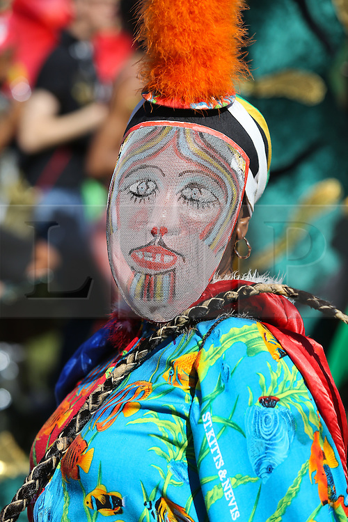 © Licensed to London News Pictures. 29/08/2016. Leeds, UK. A woman wears a traditional mask at the Leeds West Indian Carnival in Leeds, West Yorkshire. First run in the 1960's, the Leeds West Indian Carnival is Europe's longest running authentic Caribbean carnival parade. Photo credit : Ian Hinchliffe/LNP
