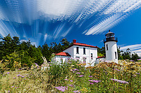 Admiralty Head Lighthouse at Fort Casey State Park stands out in this time stack photograph of a summer afternoon on Whidbey Island in Washington state.