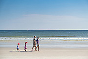 A family walks along the pristine Flagler Avenue beach in New Smyrna Beach, Florida. New Smyrna beach is known for the fine white sand that is firm enough for vehicles to drive on the sand.