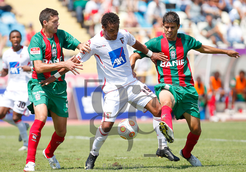 Maritimo player,Cardozo (R), fights for the ball with Braga opponent, Mgyong (C) and Miguel Angelo, during their first league soccer match held at the Barreiros stadium, Funchal, Madeira Island, Portugal, 13 Setember 2009..Photo Gregorio Cunha.Estadio dos Barreiros, Liga Portuguesa.Maritimo vs Braga.Cardozo, Mgyong e Miguel Angelo.Foto Gregorio Cunha.