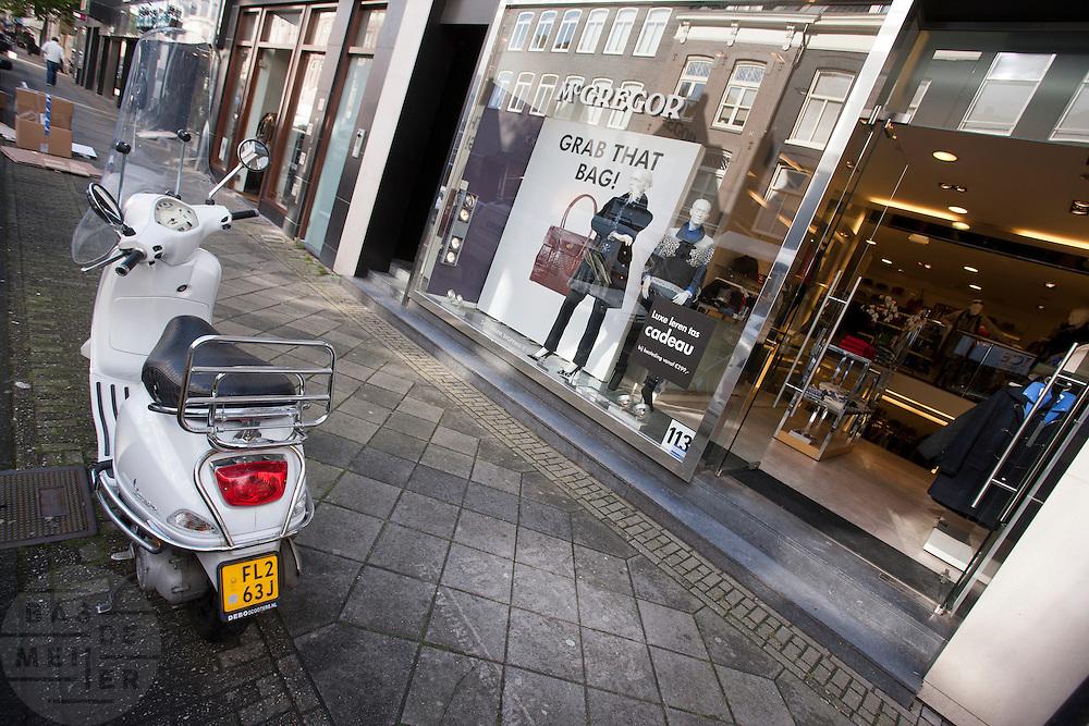 Een scooter staat voor een kledingwinkel in de PC Hooftstraat in Amsterdam.<br /> <br /> A scooter is parked at the fancy shopping area PC Hooftstraat in Amsterdam.
