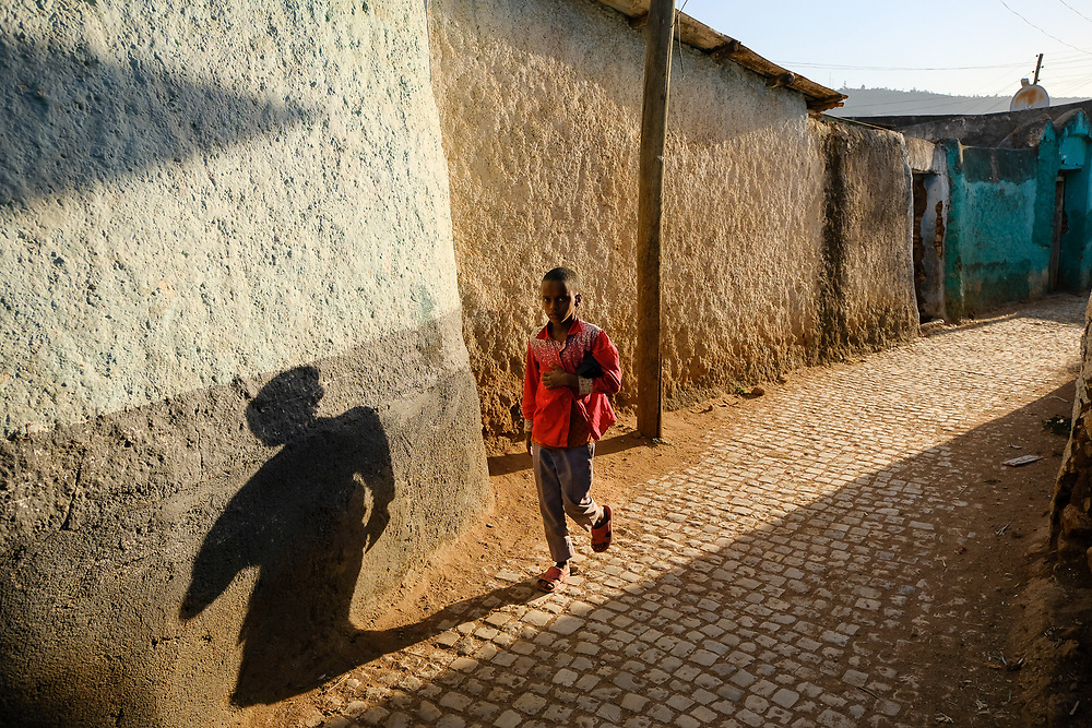 A child walks down a street in old Harar at sunset. Harar is an ancient fortified city which with its 368 alleys concentrated in one square kilometer is the most fascinating Ethiopian city. Photo by Lorenz Berna