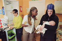 Specialist worker and residents; one holding young baby; standing in communal kitchen of women only homeless hostel,