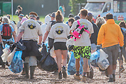 The rubbish picking team does their early morning rounds - The 2019 Glastonbury Festival, Worthy Farm. Glastonbury.