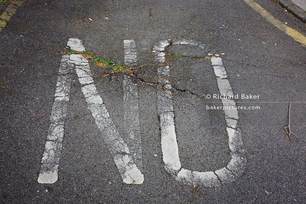 The word NO fading on a south London housing estate road surface.