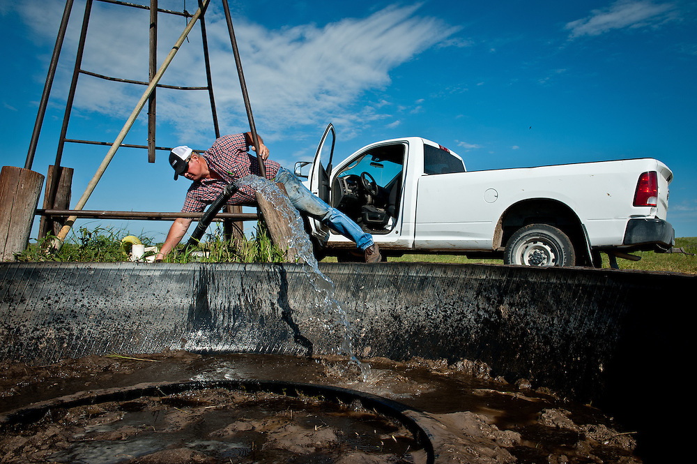 Bruce Boettcher turns on a well that will fill a giant tire harvested from a Wyoming pit mine vehicle on his Sandhills ranch in July, south of Atkinson, Nebraska.
