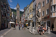 With the Zwölferturm clocktower in the distance, tourists sit beneath the St. John of Nepomuk monument in front of the Town Hall in Sterzing-Vipiteno, South Tyrol, northern Italy. The Zwölferturm is a 46m high tower erected in 1470, it is the symbol of the city that divides the New Town from Old Town Sterzing. Sterzing (Italian: Vipiteno) is a commune in South Tyrol in northern Italy. It is the main village of the southern Wipptal, and the Eisack River flows through the medieval town. It also acts as a border town - the first large town one reaches after crossing the Brenner Pass from nearby Austria.
