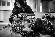 Mohammed Mohsin, 14, a boy suffering from severe cerebral palsy, is being fed water by his mother, a '1984 Gas Survivor', inside a public hospital in Bhopal, Madhya Pradesh, central India, near the abandoned Union Carbide (now DOW Chemical) industrial complex.