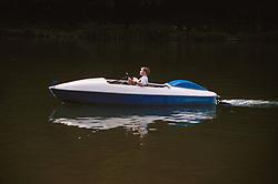 Young boy driving children's motorised boat across lake,