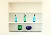 shelf in the wall with colorful bottles and glasses