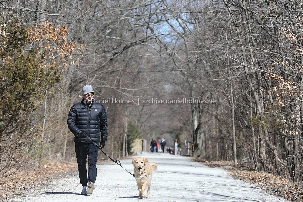 (3/16/20, HOLLISTON, MA) Sean McEntegart and his 3-year-old Golden Retriever Winston take a walk on the Rail Trail in Holliston on Monday. [Daily News and Wicked Local Photo/Dan Holmes]