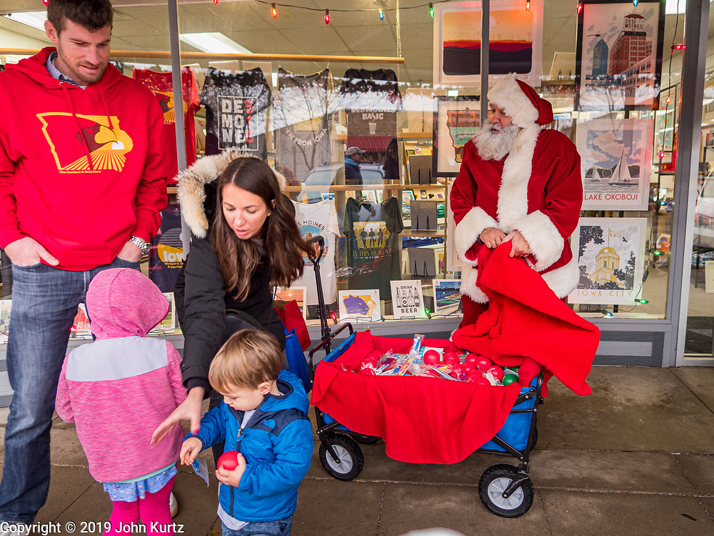 """30 NOVEMBER 2019 - WEST DES MOINES, IOWA: SANTA CLAUS talks to members of the Wilson family on 5th Street, the main business street in West Des Moines, Saturday. The Wilsons are visiting Des Moines from Arlington Heights, Illinois. Santa was handing out gifts to children on Small Business Saturday. """"Small Business Saturday"""" was first observed in the United States on November 27, 2010, as a counterpart to Black Friday and Cyber Monday, which are generally considered events at malls, """"big box"""" stores and e-commerce retailers. Small Business Saturday encourages holiday shoppers to patronize brick and mortar businesses that are small and local. Small Business Saturday is a registered trademark of American Express.       PHOTO BY JACK KURTZ"""