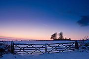 Farm gate in traditional snow scene in The Cotswolds, Swinbrook, Oxfordshire, United Kingdom