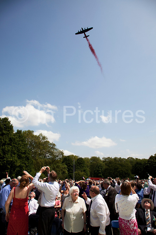 Lancaster bomber fly past drops tousands of poppies onto the crowds below. Veterans and their families gather in Green park for a service to watch as the memorial to the 55,573 airmen of Bomber Command who died during World War II was unveiled. Some 6000 attended the ceremony. Criticism of large-scale area bombing by the RAF near the end of WWII had stalled plans for a memorial for years. London, England, UK.