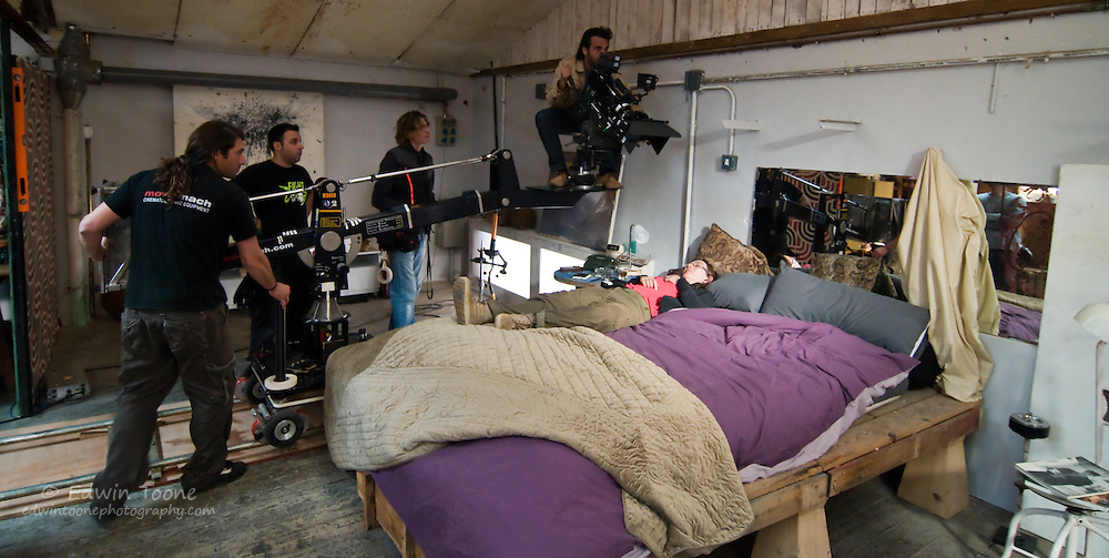 A traveling is set up and a stand-in is placed in the bed to test the lighting.