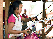 A Kayah Red Karen ethnic minority woman weaving a bag on a traditional back-strap loom on 22nd March 2016 in Kayah State, Myanmar. Myanmar is one of the most ethnically diverse countries in Southeast Asia with 135 different indigenous ethnic groups with over a dozen ethnic Karenni subgroups in the Kayah region. Unlike the older women, young Kayah women wear modern clothing every day