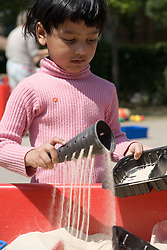 Girl playing with sand in sandpit,