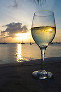 Glass of white wine on a ledge with the Marigot, St. Martin harbor at sunset as the background