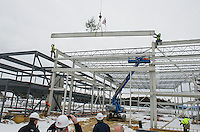 "Ethan Chalke and Jim Johnson of American Steele guide  the final beam into place with signatures of the people who have had a significant role in the project during the traditional ""Topping Off"" ceremony at the Gilford Marine Patrol building on Monday morning.  (Karen Bobotas/for the Laconia Daily Sun)"