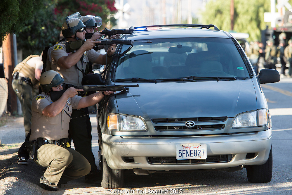 Shooting in San Bernardino.<br /> San Bernardino County Sheriffs take cover behind a mini van with their rifles and shotguns set up a south flank to contain the shooters who just engaged them.