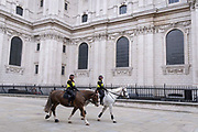 Beneath the architecture of Wrens St Pauls Cathedral, two Women Officers with the City of London Police, ride their horses on a routine daily patrol through the City of London, the capitals financial district, on 22nd June 2021, in London, England.