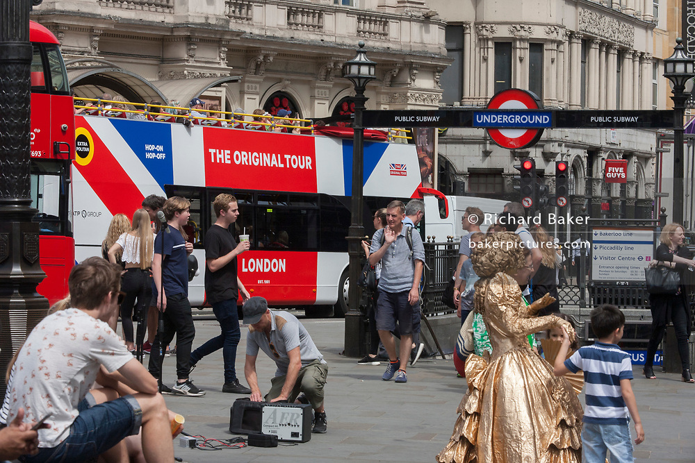 A tour bus with The Original Tour drives past street buskers in Coventry Street on its route through central London, on 7th July 2017, in London.
