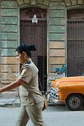 Woman wearing uniform walking down street, Havana, Cuba