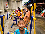 "09 AUGUST 2014 - BANGKOK, THAILAND: Children play on fitness equipment while they wait for a free meal for Ghost Month at the Ruby Goddess Shrine in the Dusit section of Bangkok. The seventh month of the Chinese Lunar calendar is called ""Ghost Month"" during which ghosts and spirits, including those of the deceased ancestors, come out from the lower realm. It is common for Chinese people to make merit during the month by burning ""hell money"" and presenting food to the ghosts. At Chinese temples in Thailand, it is also customary to give food to the poorer people in the community.        PHOTO BY JACK KURTZ"