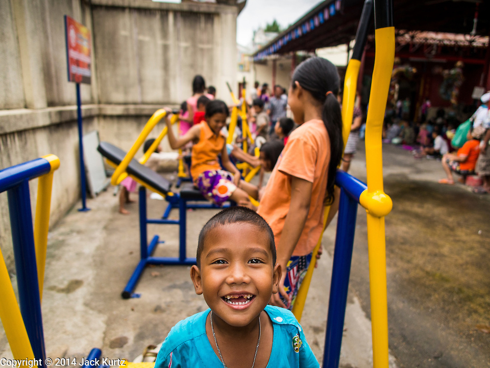 """09 AUGUST 2014 - BANGKOK, THAILAND: Children play on fitness equipment while they wait for a free meal for Ghost Month at the Ruby Goddess Shrine in the Dusit section of Bangkok. The seventh month of the Chinese Lunar calendar is called """"Ghost Month"""" during which ghosts and spirits, including those of the deceased ancestors, come out from the lower realm. It is common for Chinese people to make merit during the month by burning """"hell money"""" and presenting food to the ghosts. At Chinese temples in Thailand, it is also customary to give food to the poorer people in the community.        PHOTO BY JACK KURTZ"""