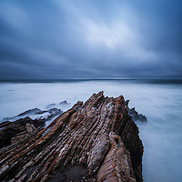 Waves crash over tidal rocks at dusk, Montana de Oro state park, California