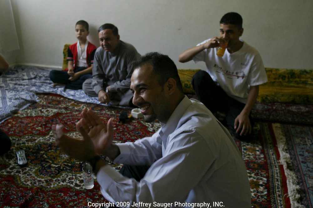 Emad Al-kasid, center, celebrates as he and his brothers, from left, Aladdin, 8, his father Malik, Sagid, 17, watch the first official meeting of Iraq's new government in his father's apartment in the Iraqi area of Damascus, Syria, Sunday, July 13, 2003. Al-kasid has been planning has been planning the trip home to Nasiriyah, Iraq, over the last year. He is visiting his immediate family is in Damascus, Syria, as hundreds of thousands of Iraqi Shiite settled in Syria after the Gulf War and their uprising against Saddam Hussein in 1991.