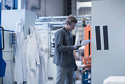 Young male engineer looking at report in an industrial plant, Freiburg Im Breisgau, Baden-W¸rttemberg, Germany