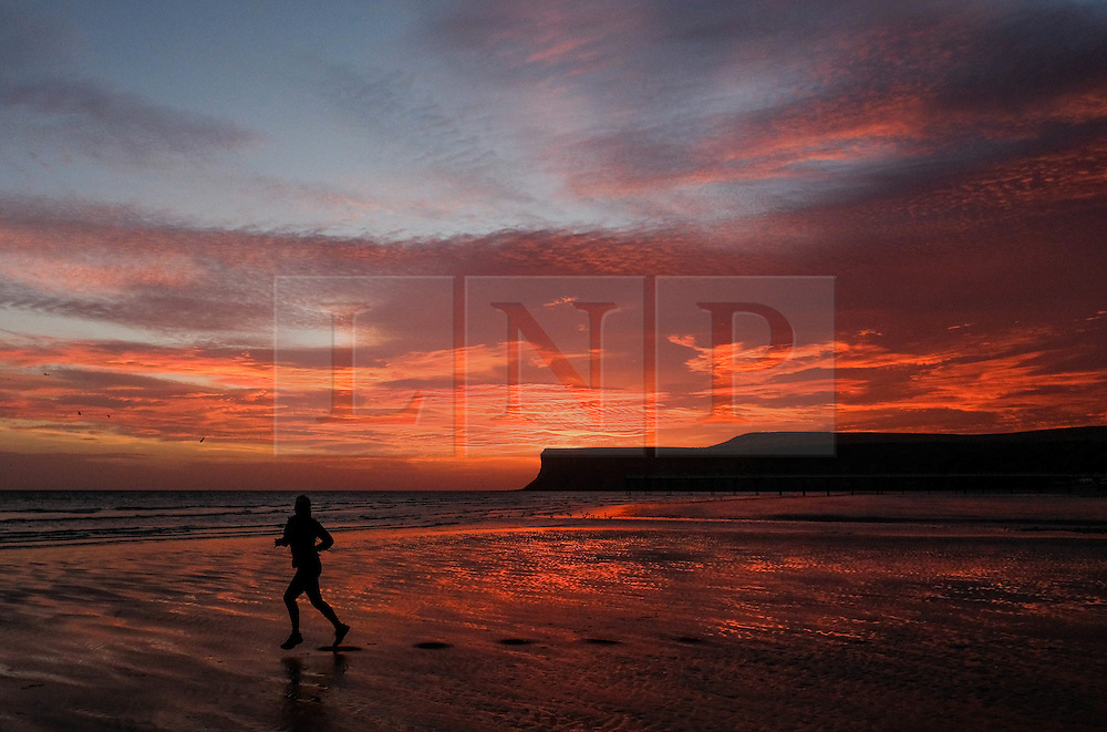 © Licensed to London News Pictures. <br /> 28/09/2016. <br /> Saltburn-by-the-Sea, UK.  <br /> <br /> A woman goes for a morning run along the beach as clouds over Saltburn by the Sea turn a dramatic orange as the sun begins to rise.<br /> <br /> Photo credit: Ian Forsyth/LNP