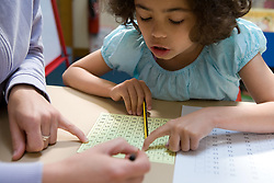 Young girl sitting at desk with teacher; working on maths problem,
