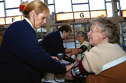 Community nurse carries out blood pressure tests on public & bus drivers at Keighley Bus Station Yorkshire UK