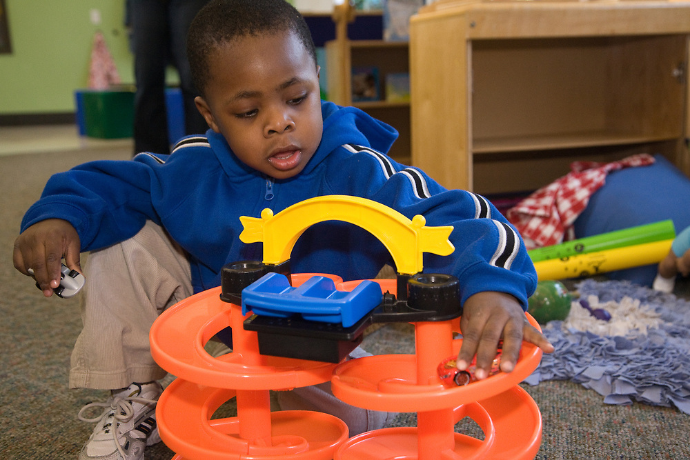 United States, Washington, Bellevue, boy playing with cars in class at Kindering Center