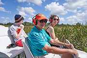Family on Florida swamp boat wearing ear protection