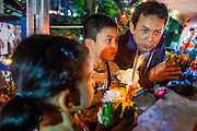28 NOVEMBER 2012 - BANGKOK, THAILAND: A man talks to his children about the Loy Krathong traditon at Wat Yannawa in Bangkok. Loy Krathong takes place on the evening of the full moon of the 12th month in the traditional Thai lunar calendar. In the western calendar this usually falls in November. Loy means 'to float', while krathong refers to the usually lotus-shaped container which floats on the water. Traditional krathongs are made of the layers of the trunk of a banana tree or a spider lily plant. Now, many people use krathongs of baked bread which disintegrate in the water and feed the fish. A krathong is decorated with elaborately folded banana leaves, incense sticks, and a candle. A small coin is sometimes included as an offering to the river spirits. On the night of the full moon, Thais launch their krathong on a river, canal or a pond, making a wish as they do so.    PHOTO BY JACK KURTZ