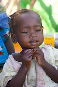 (MODEL RELEASED IMAGE). Two year old Hawa Aboubakar eating aiysh in the Breidjing Refugee Camp, Eastern Chad on the Sudanese border (which shelters 30,000 people who have fled their homes in Darfur, Sudan.) Aiysh is a the thick porridge that this refugee family eats three times a day. (Supporting image from the project Hungry Planet: What the World Eats.)