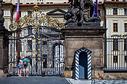 """A young couple is looking through the Prague Castle gate in-front of the Wrestling Titans (Sousoší Souboj Titánů) infront of empty Prague Castle at """"Hradcany Square"""" (Hradcanske Namesti). The Czech government lowered the security measures and as of Monday 25 May 2020, wearing of protective masks will be mandatory only in the interiors of buildings other than the place of residence and in public transport."""
