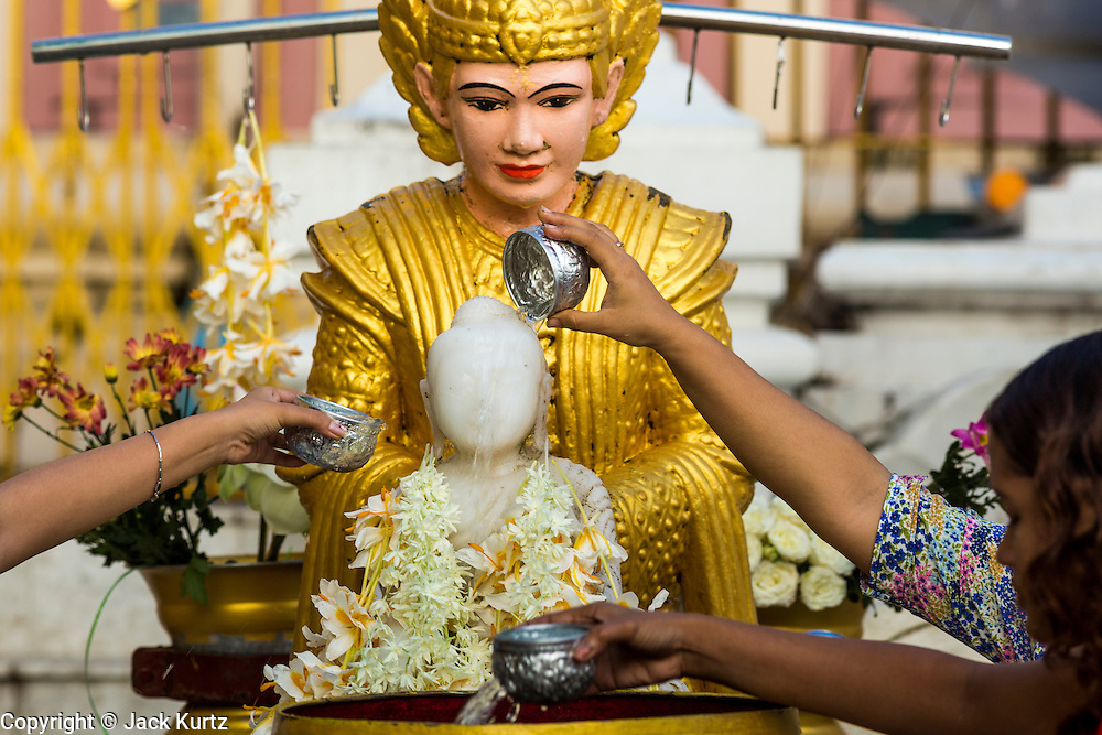 15 JUNE 2013 - YANGON, MYANMAR: People bathe a statue of the Buddha to make merit at Shwedagon Pagoda. The Shwedagon Pagoda is officially known as Shwedagon Zedi Daw and is also called the Great Dagon Pagoda or the Golden Pagoda. It is a 99 metres (325ft) tall pagoda and stupa located in Yangon, Burma. The pagoda lies to the west of on Singuttara Hill, and dominates the skyline of the city. It is the most sacred Buddhist pagoda in Myanmar and contains relics of the past four Buddhas enshrined: the staff of Kakusandha, the water filter of Koṇāgamana, a piece of the robe of Kassapa and eight strands of hair fromGautama, the historical Buddha. The pagoda was built between the 6th and 10th centuries by the Mon people, who used to dominate the area around what is now Yangon (Rangoon). The pagoda has been renovated numerous times through the centuries. Millions of Burmese and tens of thousands of tourists visit the pagoda every year, which is the most visited site in Yangon.  PHOTO BY JACK KURTZ