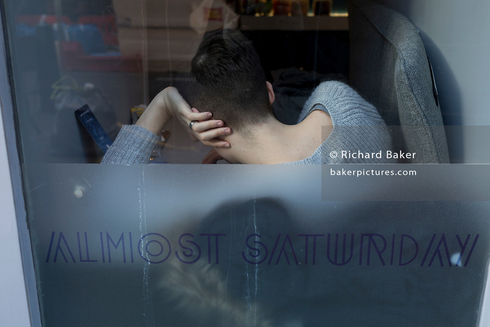 A young person with a double-jointed wrist, rests in the wondow of a cafe called Almost Saturday in central London, on 7th February 2018, in London, England.