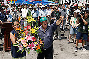 14 SEPTEMBER 2003 - CANCUN, QUINTANA ROO, MEXICO:  Rafael Allegria, a farm activist from Honduras, RIGHT, and another farm activist salute Lee Kyung-hae during a memorial service Sunday for the Korean farm activist who publicly committed suicide Wednesday in Cancun to protest World Trade Organization agricultural policies, has been built where he died in a park in Cancun. Thousands of protestors opposed to the World Trade Organization and globalization have come to Cancun to protest the WTO meetings taking place in the hotel zone. Mexican police restricted most of the anti-globalization protestors to downtown Cancun, about five miles from the convention center.  PHOTO BY JACK KURTZ