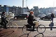 In Amsterdam fietsen twee vrouwen over het fietspad bij het Damrak.<br /> <br /> In Amsterdam two women cycle at the bike lane at the Damrak.