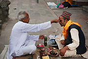 A man is receiving blessings from a hole man according to Hindu tradition inthe Pashupatinath Temple complex in Kathmandu.