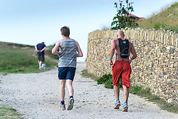 Two runners on the South West Coastal Path in Newquay.