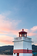 Sunset at the Brockton Point Lighthouse (built in 1914).  Photographed from Brockton Point at Stanley Park in Vancouver, British Columbia, Canada with North Vancouver, West Vancouver, and the Lions Gate Bridge in the background.