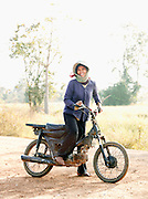 Local farming woman on her moped in rural Cambodia