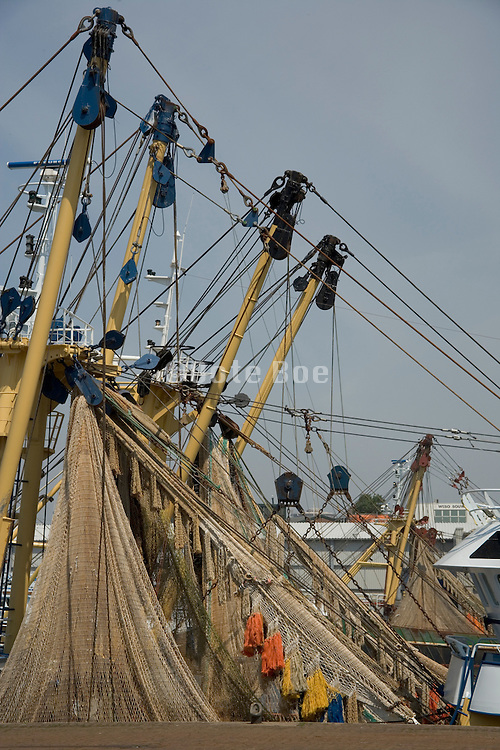 large industrial fishing boats waiting with there nets hanging to dry